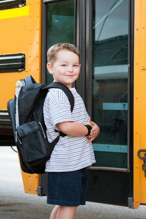 feliz: Happy young boy in front of school bus going back to school