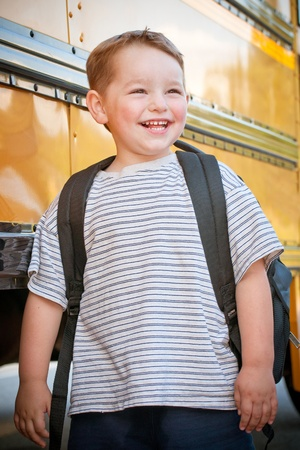 pre school: Happy young boy in front of school bus going back to school