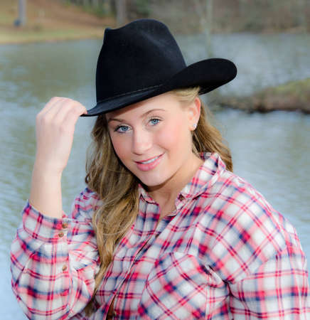 Outdoor portrait of beautiful blonde woman in western clothing
