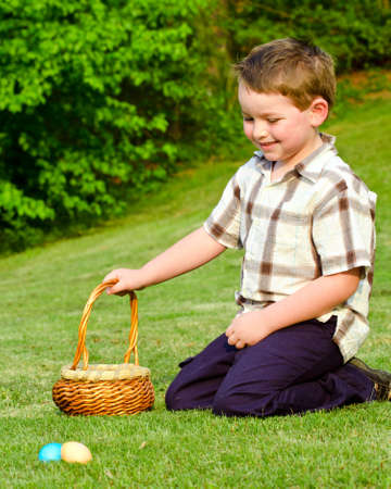 Young boy collecting easter eggs on hunt Banco de Imagens
