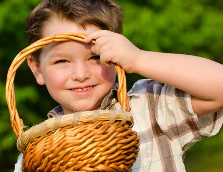 Young boy looking through easter basket on easter egg hunt photo