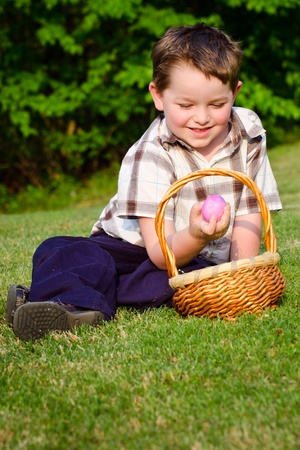 Young boy collecting easter eggs on hunt photo