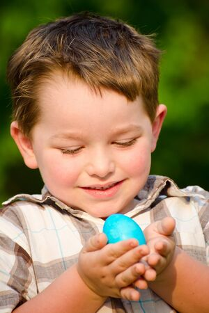 Boy holding easter egg on easter egg hunt photo