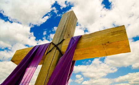 resurrected: Cross with purple drape or sash for Easter with blue sky and clouds in background