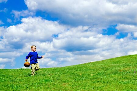 hunts: Easter egg hunt with young boy running with basket to collect Easter Eggs