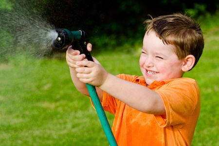 sprinkler: Child plays with water hose outdoors during summer or spring to cool off in hot weather