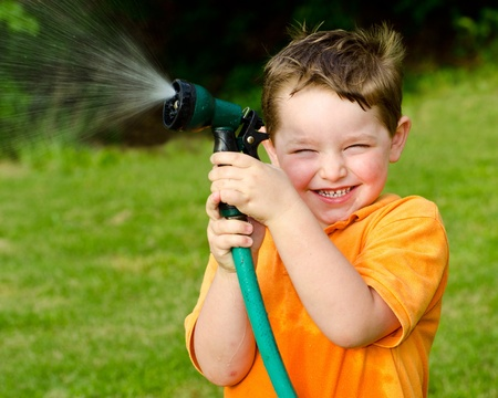 cool kids: Child plays with water hose outdoors during summer or spring to cool off in hot weather