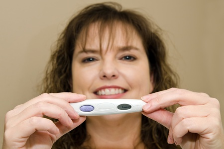 Close up of positive pregnancy test with happy, smiling middle-aged woman in background Stock Photo - 13116423