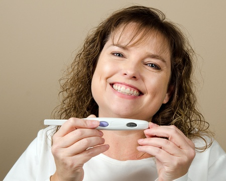 Happy middle-aged woman holding a positive pregnancy test Stock Photo - 13116424