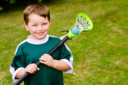 Happy young child lacrosse player with his stick photo