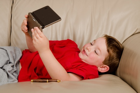 couch: Couch potato concept of boy playing video game while resting on sofa