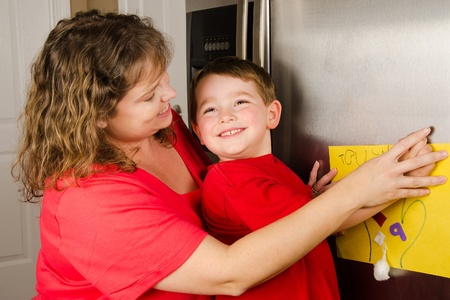 fridge: Mother and child putting up boy s art on family refrigerator at home Stock Photo