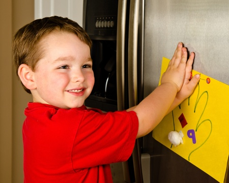 fridge: Child putting his art up on family refrigerator at home