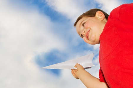 Child playing with paper airplane photo
