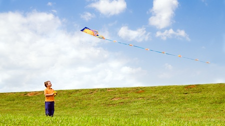 Child flying kite and playing outdoors at park Imagens