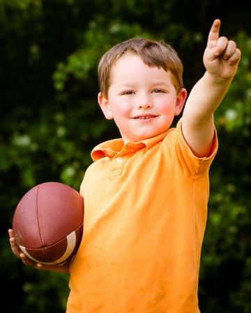 Kind met voetbal te vieren door te laten zien dat hij nummer 1 Stockfoto