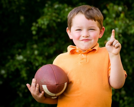Child with football celebrating by showing that he s Number 1 photo