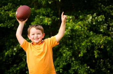american content: Child with football celebrating by showing that he s Number 1