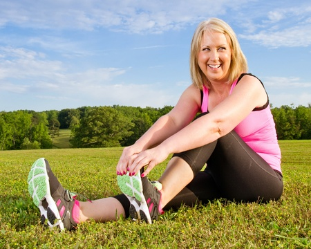 Middle-aged woman in her 40s stretching for exercise outdoors photo
