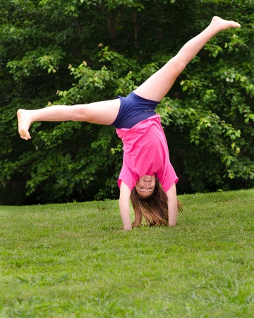 Young girl doing a cartwheel outdoors at park photo