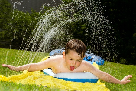 cool off: Happy child on water slide to cool off on hot day during spring or summer