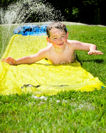 Happy child on water slide to cool off on hot day during spring or summer