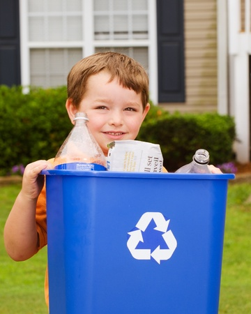 papelera de reciclaje: Reciclaje de concepto con el ni�o lleva papelera de reciclaje a la acera en su casa
