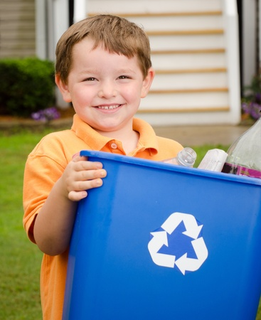 blue bin: Recycling concept with young child carrying recycling bin to the curb at his house