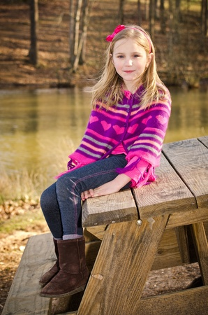 冬や早春の肖像画を着てきれいな若い女の子子供のニット ポンチョ公園で 写真素材