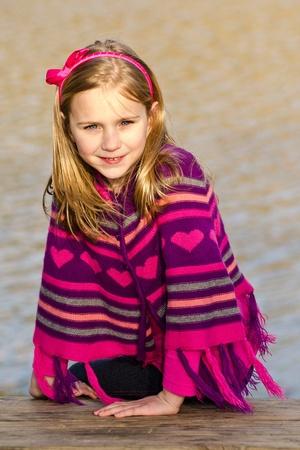 冬や早春着てかなり若い女の子子供肖像画ニット ポンチョ公園で