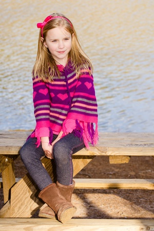 sweater girl: Winter or early spring portrait of pretty young girl child wearing knit poncho at park