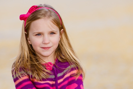 Winter or early spring portrait of pretty young girl child wearing knit poncho at park photo