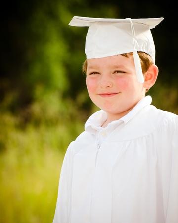 Chico joven con toga y birrete de graduaci�n de preescolar Foto de archivo - 13540758