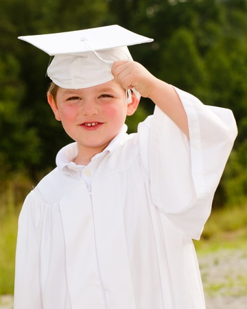 Young boy with cap and gown for preschool graduation photo