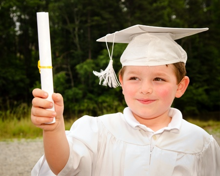 Young boy with cap and gown and certificate for preschool graduation photo
