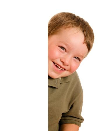 enfants qui rient: Portrait de l'enfant gar�on heureux jeune furtivement autour du coin isol� sur blanc