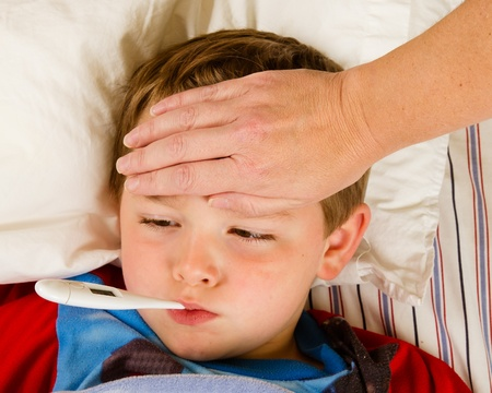 Sick child boy being checked for fever and illness while resting in bed photo