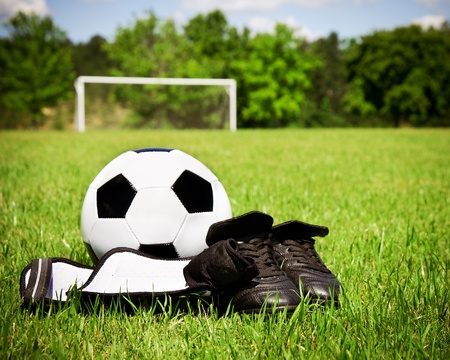 Child sports concept with soccer ball, cleats, shin guards on field Foto de archivo