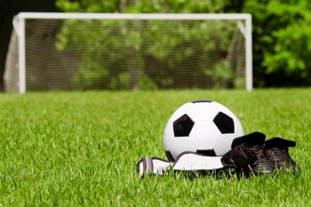 field  soccer: Deporte infantil concepto con el bal�n de f�tbol, ??tacos, espinilleras en el campo