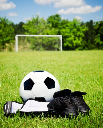 football cleats: Child sports concept with soccer ball, cleats, shin guards on field Stock Photo