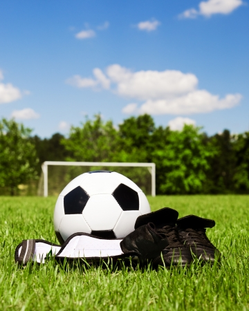 Child sports concept with soccer ball, cleats, shin guards on field photo