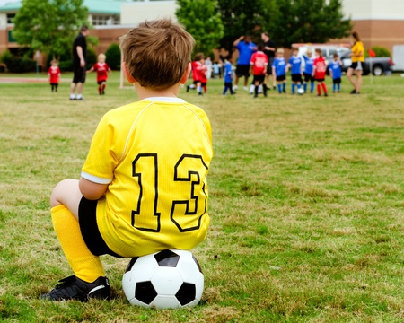 children at play: Young boy child in uniform watching organized youth soccer or football game from sidelines
