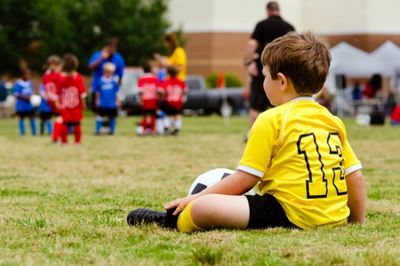 Young boy child in uniform watching organized youth soccer or football game from sidelines photo