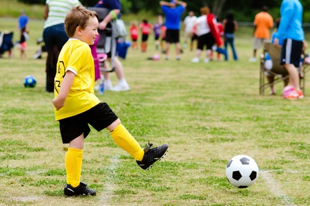 children at play: Young child boy playing soccer during organized league game