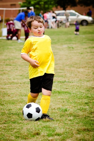 Young child boy playing soccer during organized league game photo