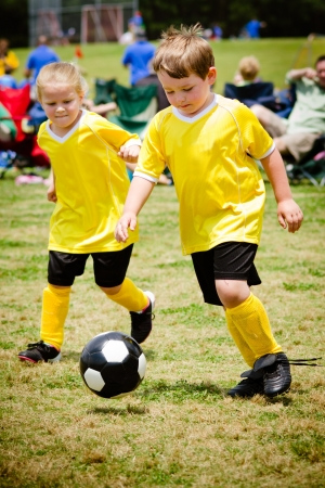 Children playing soccer in organized youth game photo