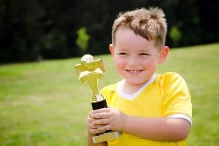trofeo: Jugador de f�tbol joven en uniforme con su nuevo trofeo Foto de archivo