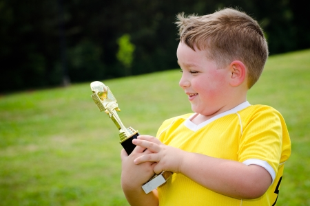 Young soccer player in uniform with his new trophy photo