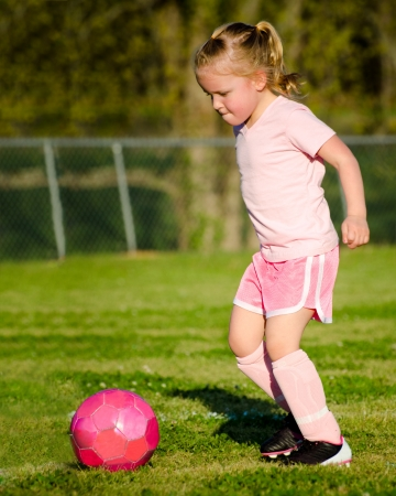 Cute young girl in pink playing soccer on field photo