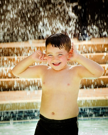 Child playing under waterfall at pool  photo